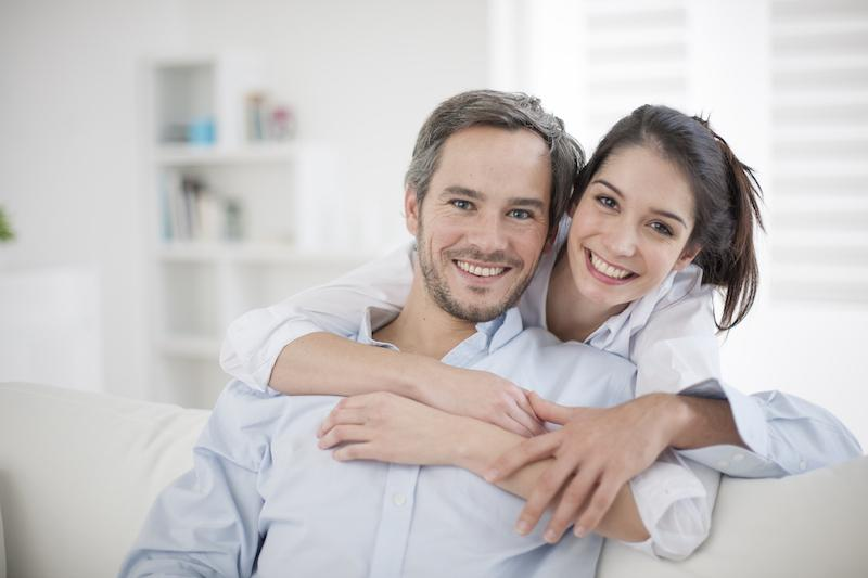 Couple sitting on the couch smiling wearing dental veneers near 62702