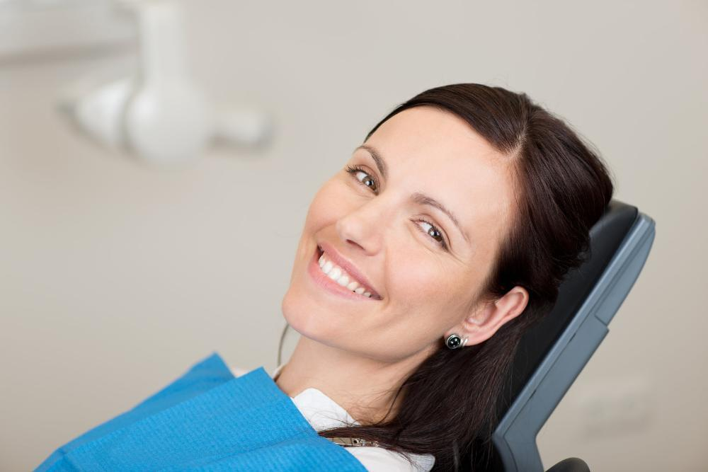 woman smiling in dental chair after cleaning